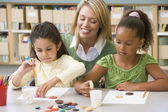 Kindergarten teacher sitting with students in art class, — Stock Photo