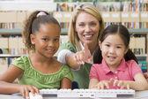 Kindergarten teacher sitting with children at computer — Stock Photo