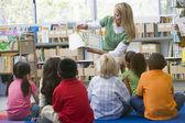 Insegnante di scuola materna, lettura per bambini in biblioteca — Foto Stock