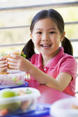 Girl eating lunch at kindergarten — Stock Photo