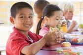 Kindergarten children eating lunch — Stock Photo
