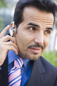 Businessman using bluetooth earpiece — Stock Photo