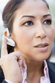 Woman using bluetooth earpiece — Stock Photo