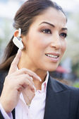 Businesswoman using bluetooth earpiece — Stock Photo