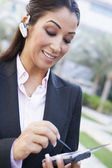 Businesswoman using bluetooth earpiece and PDA — Stock Photo