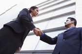 Two businessmen shaking hands outside office building — Stock Photo