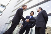 Business shaking hands outside office — Stok fotoğraf
