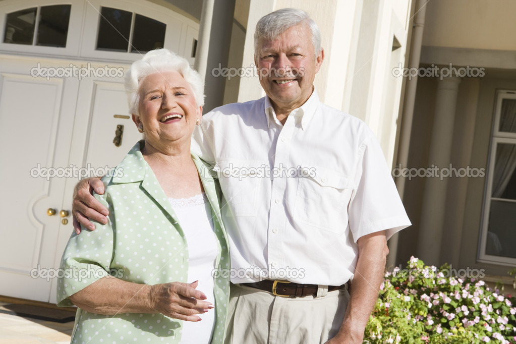 Senior couple standing outside front door of home — Stock Photo #4752854