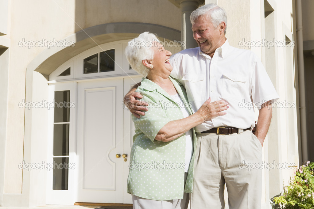 Senior couple standing outside front door of home — Stock Photo #4752856