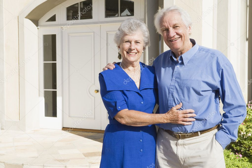 Senior couple standing outside house — Stock Photo #4752873