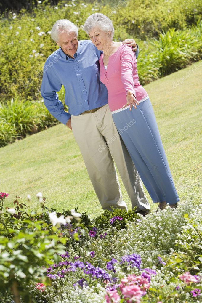 Senior couple standing in garden admiring flowerbed — Stock Photo #4752930