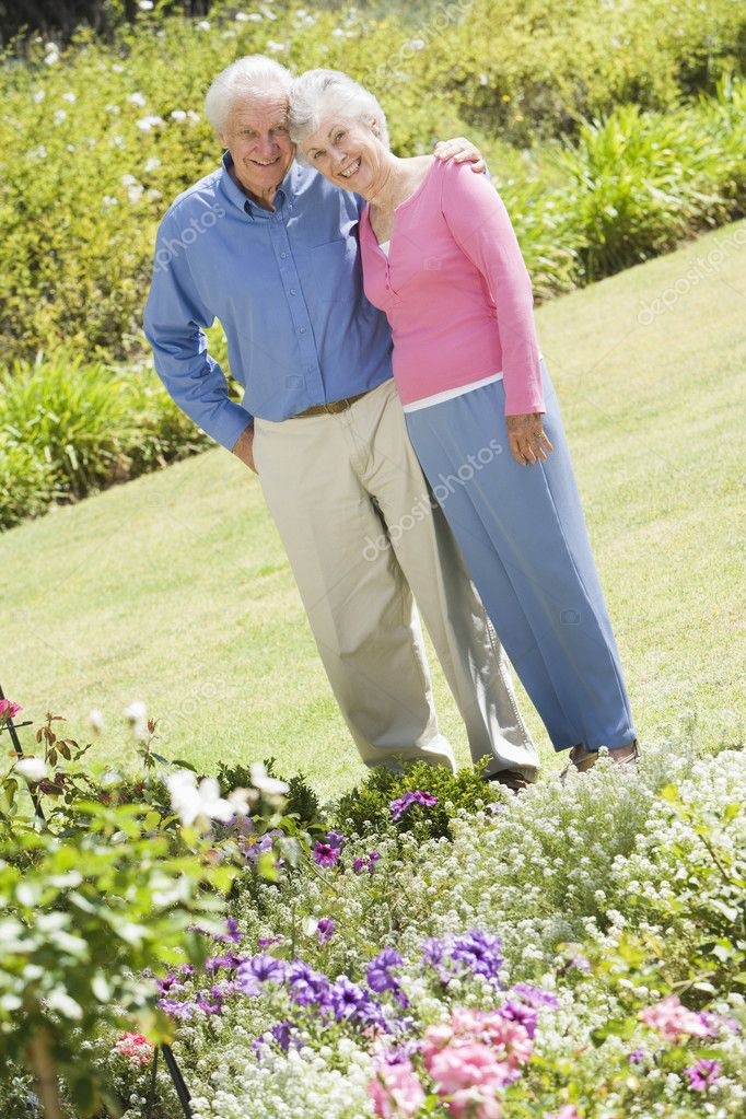 Senior couple standing in garden admiring flowerbed — Stock Photo #4752931