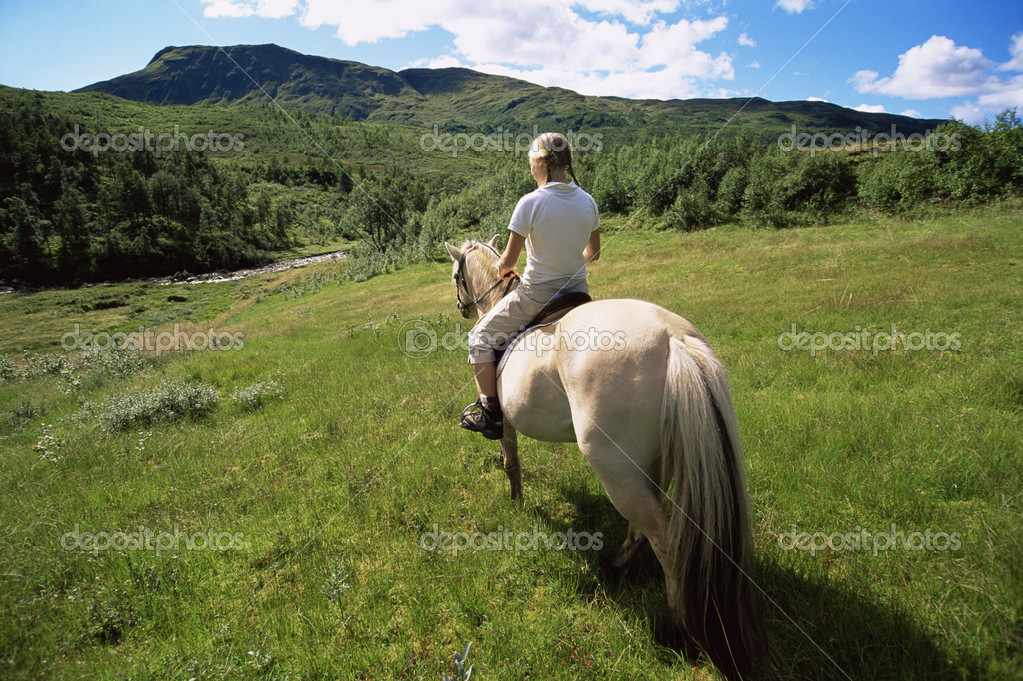 Rear view of young woman riding horse in rural setting — Stock Photo #4754442