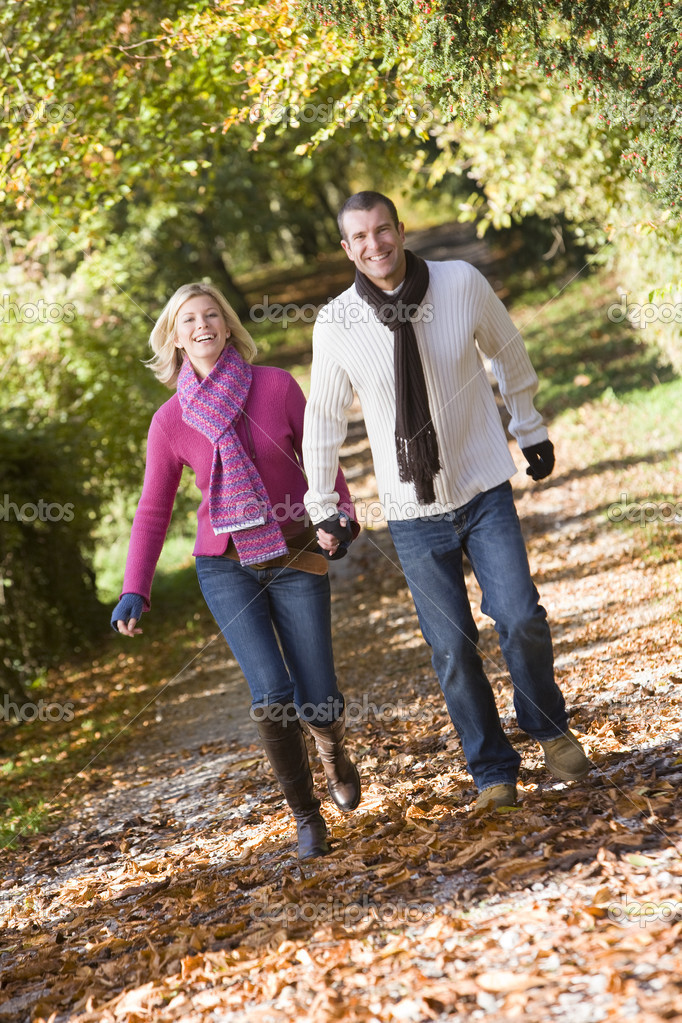 Couple holding hands on walk through autumn woods — Lizenzfreies Foto #4754883