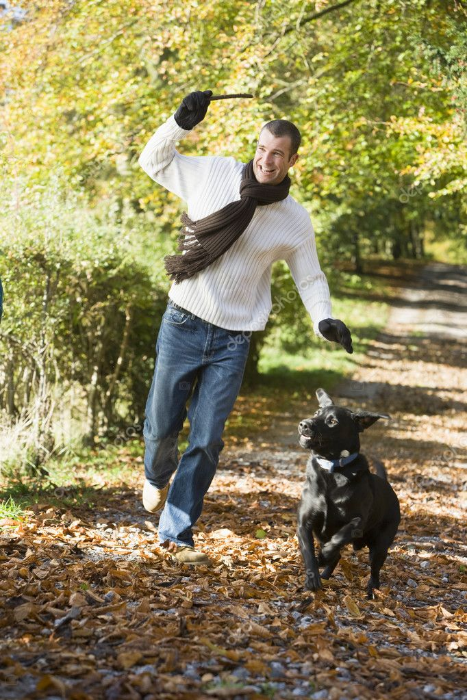 Man exercising dog in autumn woodland — Stock Photo #4754884