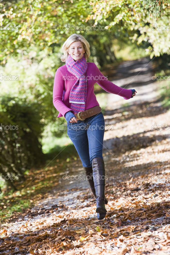 Woman running along autumn path looking to camera — Stock Photo #4754885