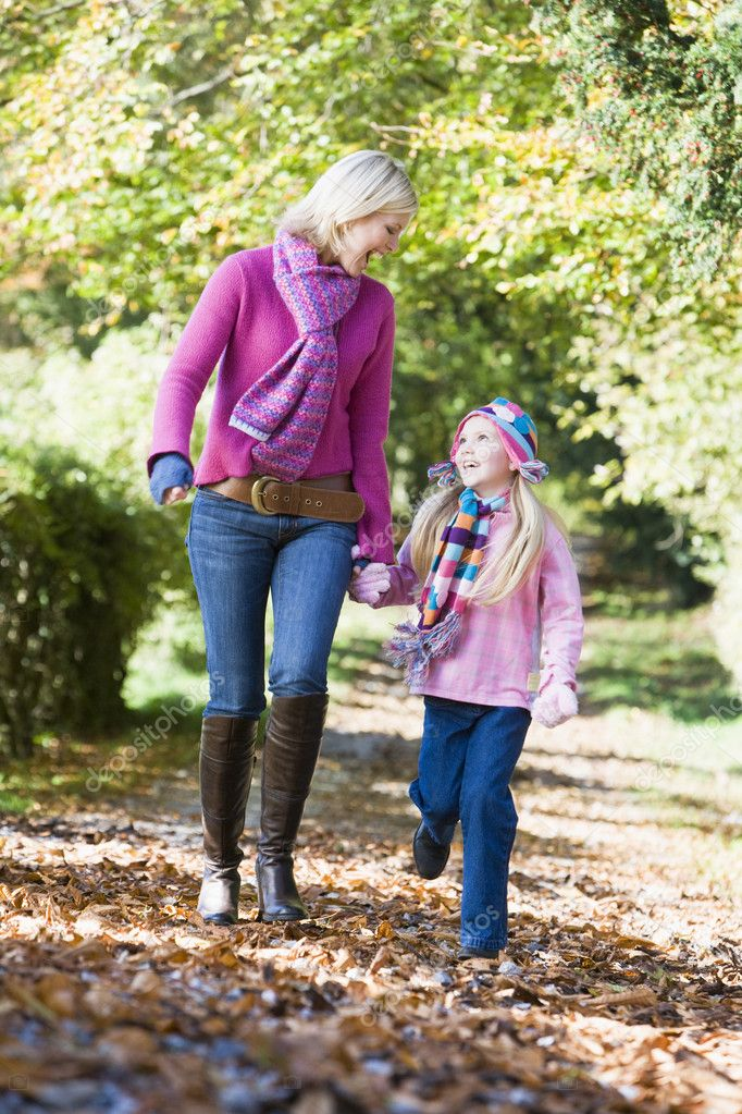 Mother and daughter walking along autumn path through trees  Stock Photo #4754887