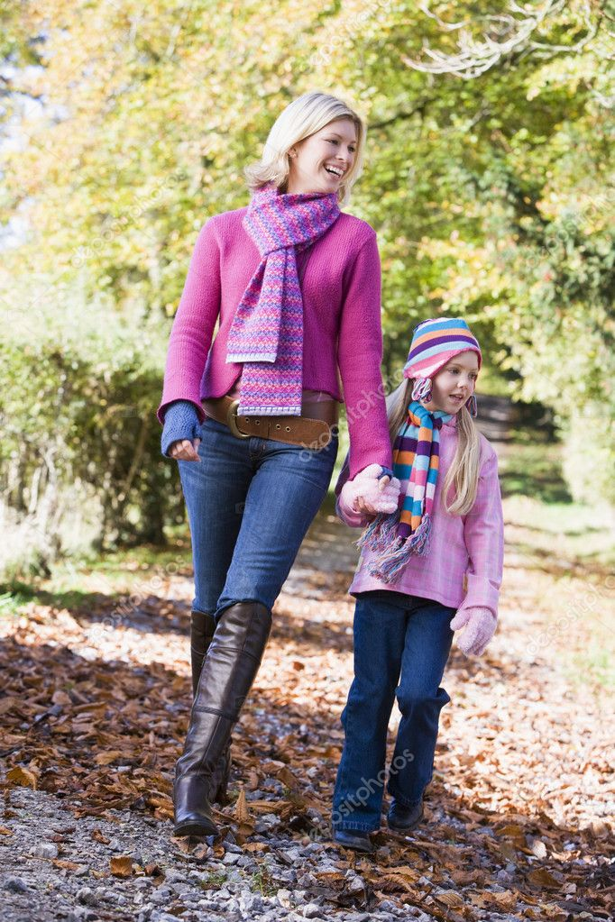 Mother and daughter walking along woodland path in autumn  Stock Photo #4754889