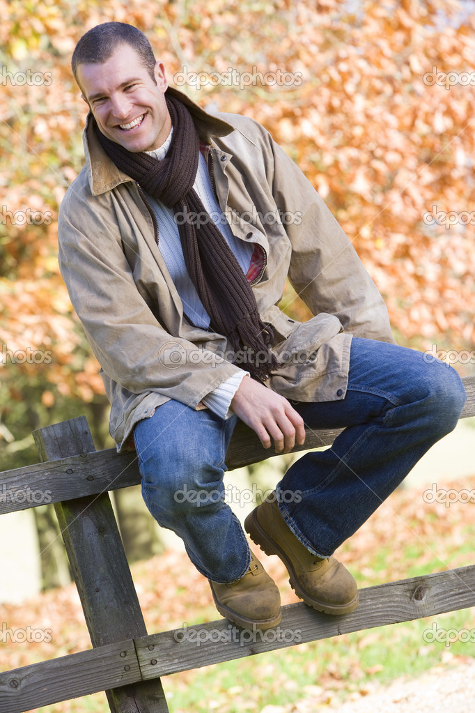 Young man sitting on fence with autumn leaves behind — Stock Photo #4754916