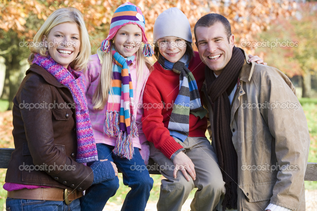 Family on autumn walk sitting on fence  Stock Photo #4754926