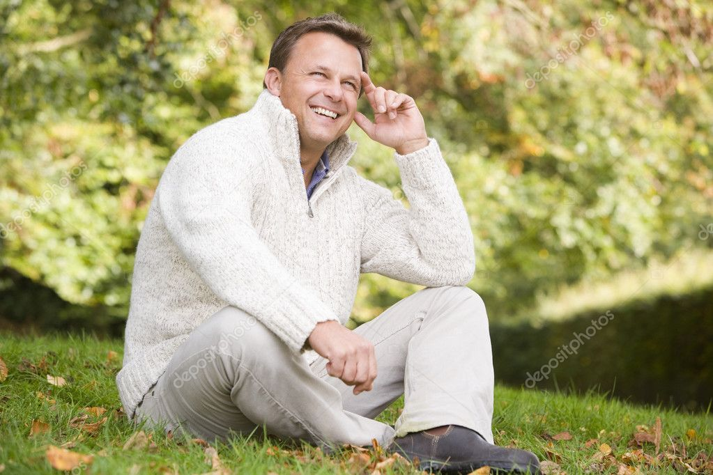 Man sitting outside on grass in autumn landscape  Stock Photo #4755056