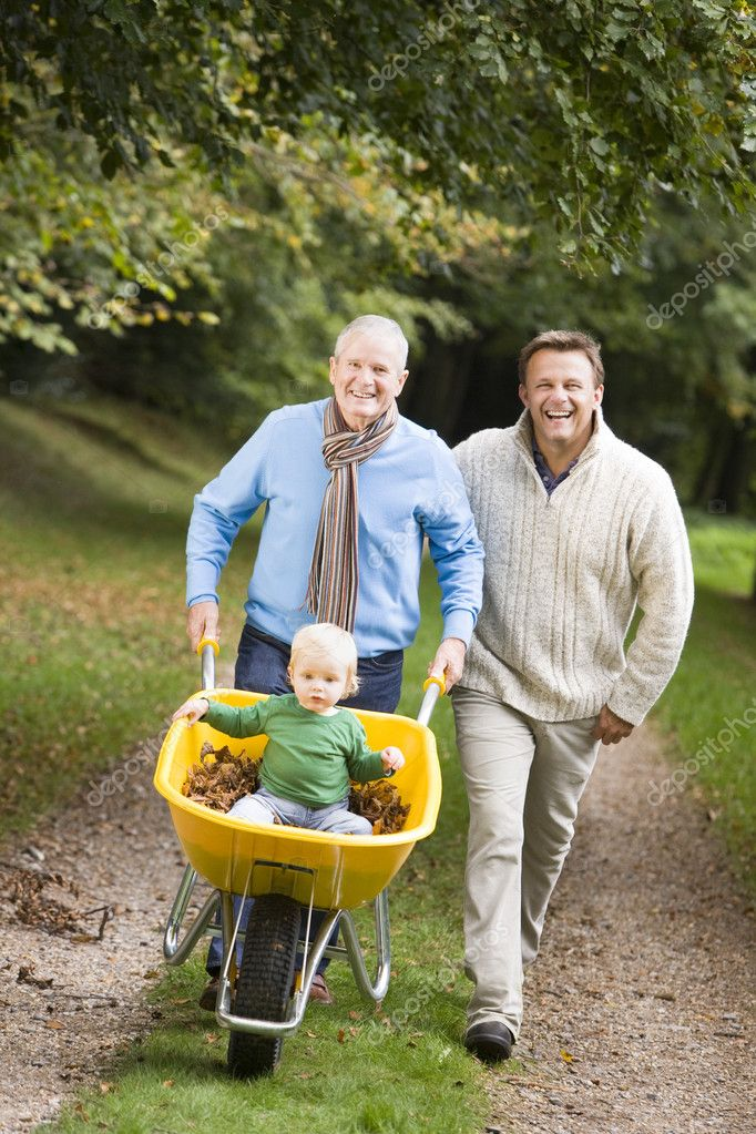 Grandfather with grandson and son pushing wheelbarrow along autumn path  Stock Photo #4755104