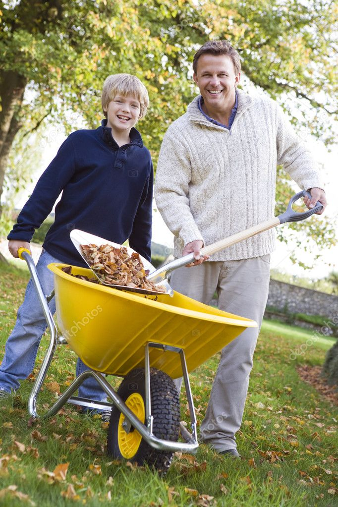 Son helping father to collect leaves in wheelbarrow — Stock Photo #4755151