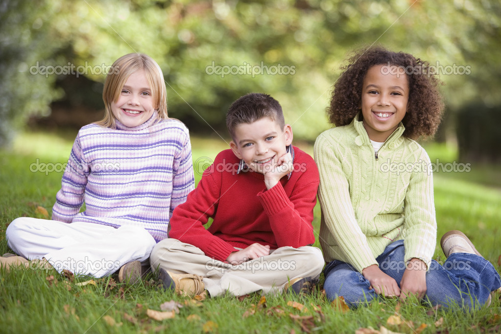 Group of children sitting in garden looking to  camera — Stock Photo #4755155
