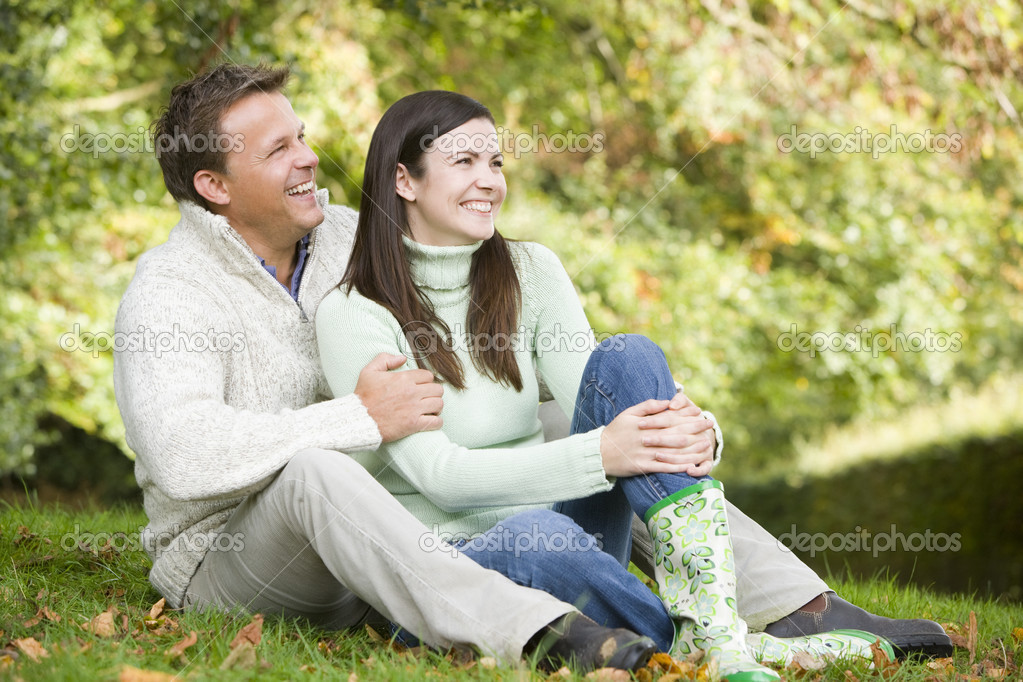 Young couple sitting on grass in autumn woods  Stock Photo #4755160