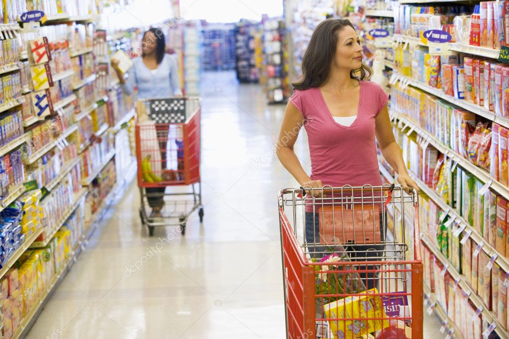 Two women pushing trolleys along supermarket aisle — Stock Photo #4757732