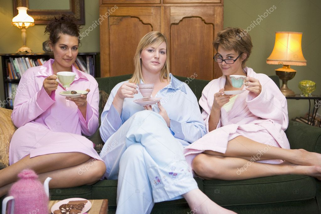 Three young women drinking tea together in their pyjamas  Stock Photo #4758715