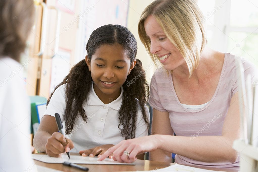 A schoolgirl sitting with her teacher in class  Stock Photo #4759541