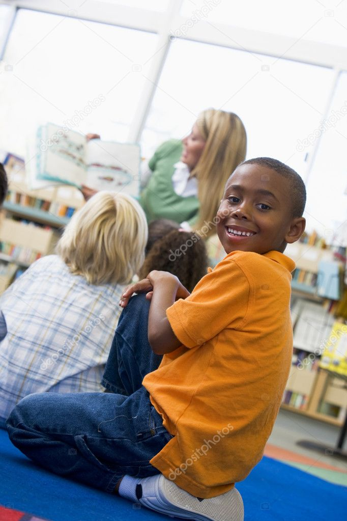 Kindergarten teacher reading to children in library, boy looking — Stock Photo #4759724