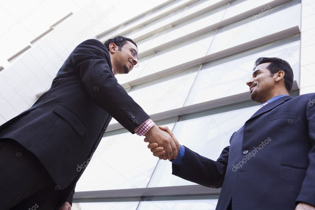 Two businessmen shaking hands outside modern office building — Stock Photo #4759907