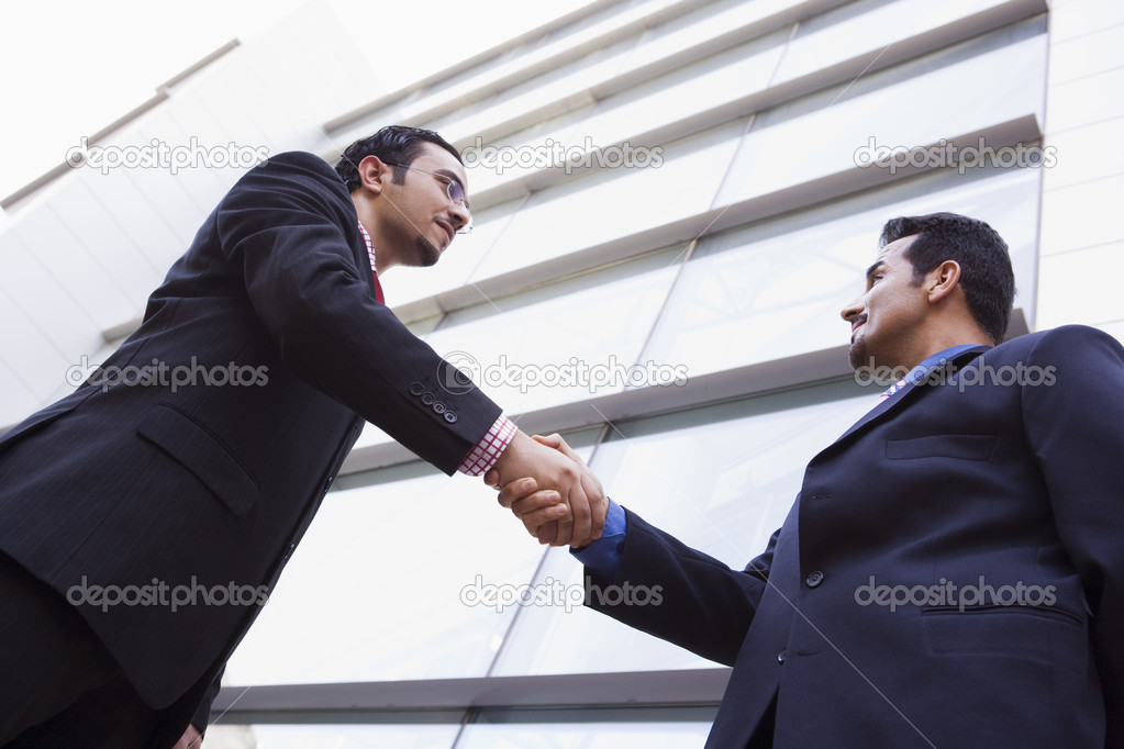 Two businessmen shaking hands outside modern office building — Stock Photo #4759910