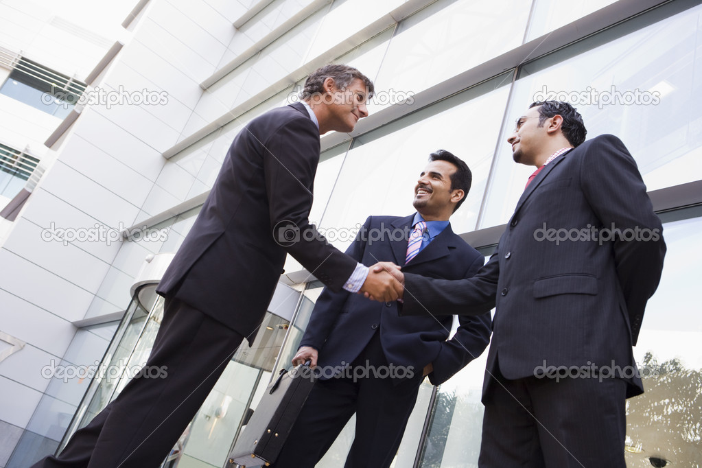 Business shaking hands outside modern office building — Stok fotoğraf #4759931