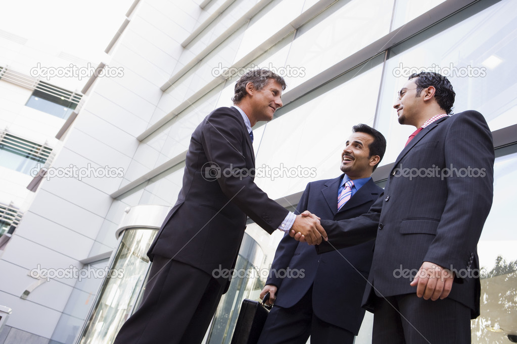 Group of businessmen shaking hands outside office building  Stock Photo #4759935