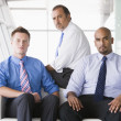 Group of businessmen sitting in lobby - Stock Photo