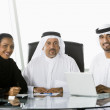 Two Middle Eastern businessmen and a woman beside a laptop — Stock Photo