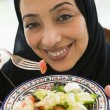 A Middle Eastern woman with a plate of salad — Stock Photo #4760334