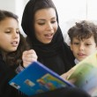 A Middle Eastern family reading a book together — Stock Photo #4760342