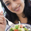 A Middle Eastern woman holding a salad up to the camera — Stock Photo #4760469