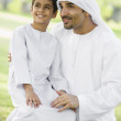 A Middle Eastern man and his son sitting in a park — Stock Photo #4760630