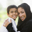 A Middle Eastern woman and her son sitting in a park — Stock Photo