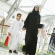 A Middle Eastern woman and her son in a shopping mall — Stock Photo