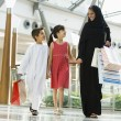 A Middle Eastern woman with two children in a shopping mall — Stock Photo #4760675