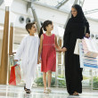 A Middle Eastern woman with two children in a shopping mall — Stock Photo
