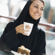 A Middle Eastern woman enjoying a meal in a restaurant — Stock Photo #4760718