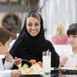 A Middle Eastern family enjoying a meal in a restaurant — Foto de Stock