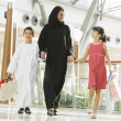 A Middle Eastern woman with two children in a shopping mall - Foto Stock